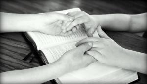 Holding Hands Bible_Stockphoto